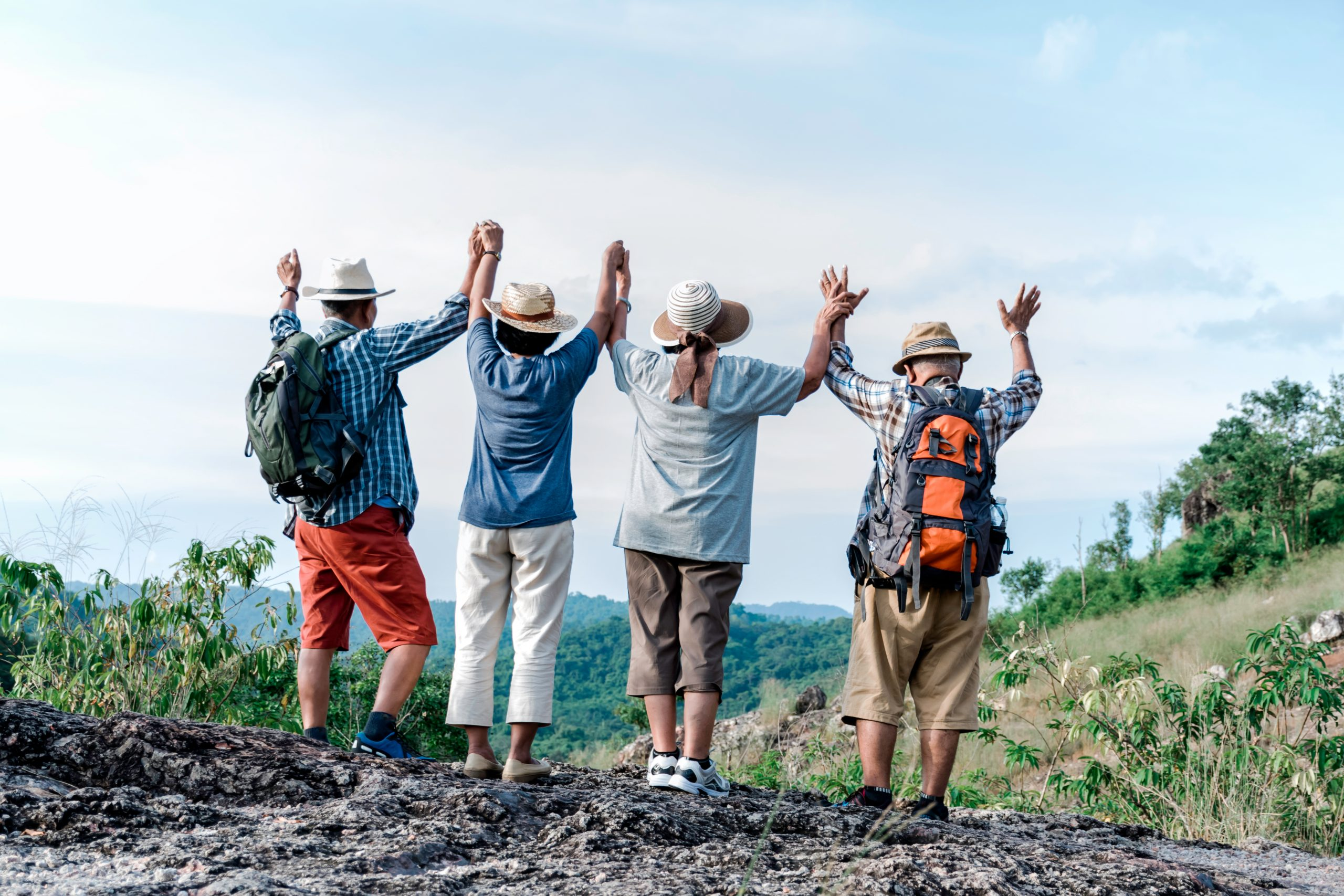 group-of-elders-travellers-holding-hands-in-the-air